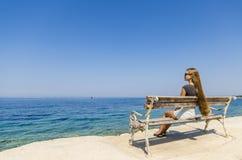 Jonge meisjeszitting op bank en het kijken op zee Royalty-vrije Stock Fotografie