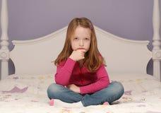 Jonge meisjeszitting op bed stock afbeeldingen