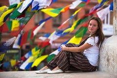 Jonge meisjeszitting op Boeddhistische stupa, gebedvlaggen die op achtergrond vliegen Reis Stock Afbeeldingen