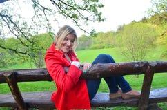 Jonge meisjeszitting op de bank in het park Stock Foto's