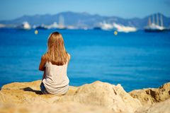 Jonge meisjeszitting op de overzeese kust royalty-vrije stock afbeelding