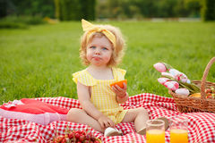 Jonge meisjeszitting op deken in park stock foto's