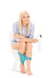 Jonge meisjeszitting op een toilet en holdingstoiletpapier Stock Foto's
