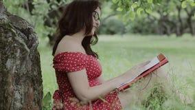 Jonge meisjeszitting op gras in het kader van boom en het schrijven nota's stock videobeelden