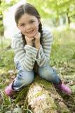 Jonge meisjeszitting op logboek Royalty-vrije Stock Foto's