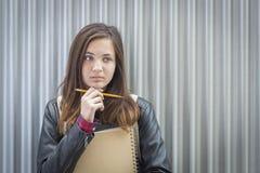 Jonge Melancholische Vrouwelijke Student With Books Looking aan de Kant Stock Afbeelding