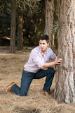 Jonge mens achter een boom Stock Fotografie