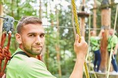 Jonge mens als beginner op een het beklimmen cursus stock fotografie