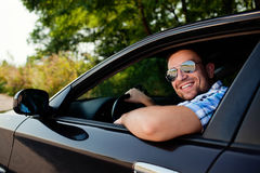 Jonge mens in auto het glimlachen Stock Foto