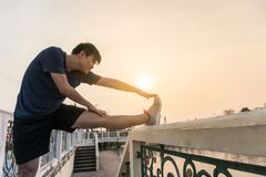 Jonge mens Aziaat die een been in het park uitrekken Royalty-vrije Stock Foto's