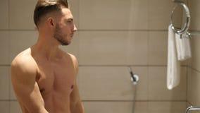 Jonge mens in badkamers, bespuitende deodorant op oksels stock footage