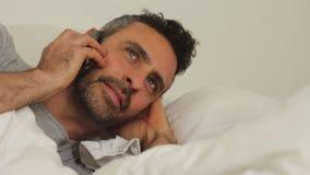 Jonge mens in bed met telefoon stock video