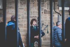 Jonge mens bekleed in een traditioneel Schots geruit Schots wollen stof die de Schotse doedelzak spelen stock afbeelding