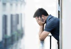 Jonge mens bij balkon in depressie die aan emotionele crisis en zorg lijden Stock Foto's