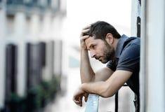 Jonge mens bij balkon in depressie die aan emotionele crisis en zorg lijden Royalty-vrije Stock Afbeeldingen