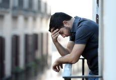 Jonge mens bij balkon in depressie die aan emotionele crisis en zorg lijden Royalty-vrije Stock Foto's
