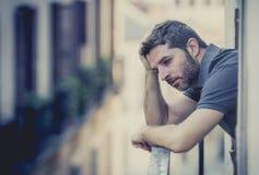 Jonge mens bij balkon in depressie die aan emotionele crisis lijden Stock Foto