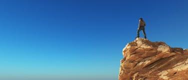 Jonge mens bij de bovenkant van de berg Royalty-vrije Stock Foto's