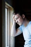 Jonge mens bij het venster Royalty-vrije Stock Afbeeldingen