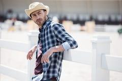 Jonge mens in bij houten omheining leunen en cowboyhoed die weg eruit zien royalty-vrije stock afbeeldingen