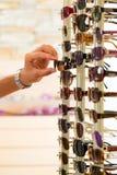 Jonge mens bij opticien het winkelen zonnebril Stock Foto