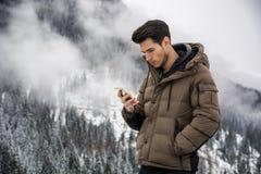 Jonge mens binnen bij berg die celtelefoon met behulp van Royalty-vrije Stock Foto