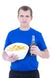 Jonge mens in blauwe eenvormige het letten op TV met bier en spaanders isolat Stock Foto