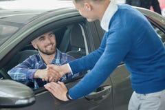 Jonge mens in blauwe sweater die vriend helpen die voertuig kiezen royalty-vrije stock afbeeldingen