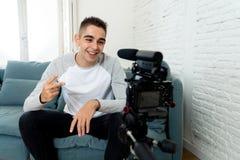 Jonge mens blogger in zijn jaren '20 die een video op camera voor aanhangers op Internet registreren stock foto