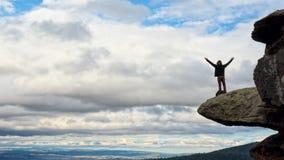 Jonge mens bovenop een klip stock afbeelding