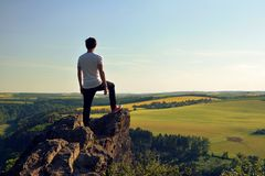 Jonge mens bovenop rots Stock Afbeelding