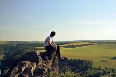 Jonge mens bovenop rots Stock Afbeeldingen