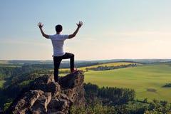 Jonge mens bovenop rots Stock Foto's