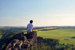 Jonge mens bovenop rots Stock Foto
