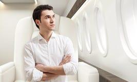Jonge mens in commerciële klasse van een vliegtuig Stock Fotografie
