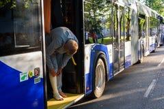 Jonge mens, danser en deelnemer die van Dansviering zich met verwond been bij bus bevinden royalty-vrije stock afbeeldingen
