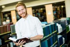 Jonge mens in de bibliotheek Stock Foto