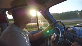 Jonge mens in de handen van de hoedenholding op een stuurwiel en het drijven van een retro auto met zongloed bij achtergrond Kauk stock videobeelden