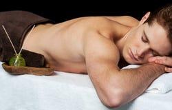 Jonge mens in de salon van de kuuroordmassage Stock Foto