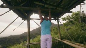 Jonge mens de spieren van de opleidingsmaag op dwarsbalk op tropische aardachtergrond Atletenmens die abs doen die opleiden stock videobeelden