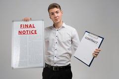 Jonge mens definitief die bericht houden en contract die op lichte achtergrond wordt geïsoleerd stock fotografie