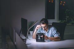 Jonge mens die aan computer bij nacht in donker bureau werken stock afbeelding