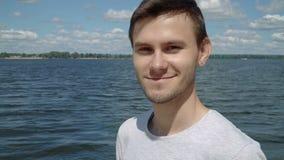 Jonge mens die aan de camera glimlachen stock footage