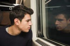 Jonge mens die aan de gang het kijken uit venster reizen Stock Foto's