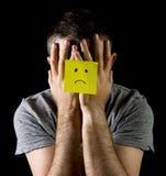 Jonge mens die aan depressie en spanning alleen met de droevige nota van de gezichtspost-it lijdt Royalty-vrije Stock Foto's