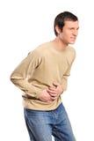 Jonge mens die aan een slechte pijn van de maagpijn lijdt Stock Foto