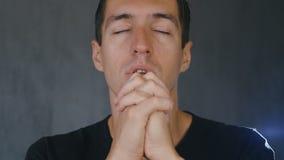 Jonge mens die aan God bidden die een kruis in zijn hand houden Concept geloof en godsdienst stock videobeelden