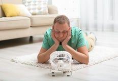Jonge mens die aan hitte voor kleine ventilator lijden stock afbeeldingen