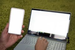Jonge mens die aan laptop en smartphone thuis werken Moderne laptop en cellphone met de witte lege schermen Freelancer gebruikt m royalty-vrije stock foto