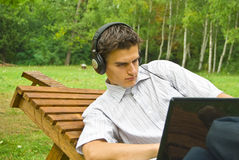 Jonge mens die aan laptop in het park werkt Stock Foto's